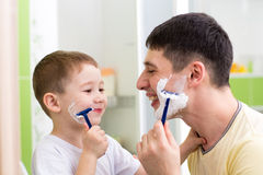Playful father and son shaving together at home bathroom. Playful father and kid son shaving together at home bathroom Stock Photos