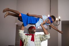 Playful father and son in superhero costume at home. Playful father and son in superhero costume playing at home Stock Images