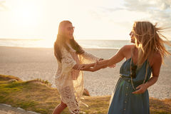 Playful female friends on a sidewalk along the beach. Two young female friends on a sidewalk along the beach playing. Young women having fun on the sea shore Stock Photography