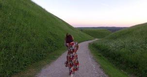 Playful female model walking on gravel path between mountains. Handheld follow. Shot stock video