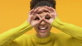 Playful female student showing binocular gesture front of eyes, having fun. Stock footage stock footage