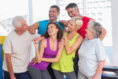 Playful friends looking at man at fitness studio Royalty Free Stock Photos
