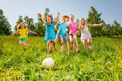 Playful friends running to the ball in field stock photo