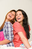 Playful friends sitting back-to-back and laughing Stock Images