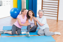 Playful friends sitting on exercise mat in gym Royalty Free Stock Image