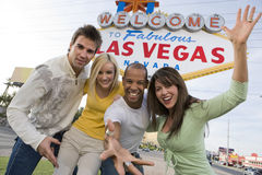 Playful Friends Standing Together Against 'Welcome To Las Vegas' Sign Stock Images