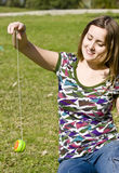Playful girl. Young woman playing yo-yo in the park Stock Photo