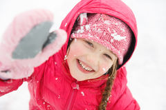 Playful girl with braids, enjoying winter and snow Stock Image