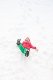 Playful girl with braids playing in the first snow royalty free stock photos