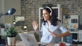 Playful girl dancing enjoying music in headphones and using laptop in office