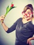 Playful girl having fun with flower tulip. Stock Photo