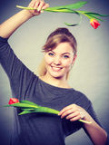 Playful girl having fun with flowers tulips. Stock Photo