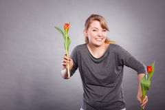 Playful girl having fun with flowers tulips. Stock Images