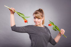 Playful girl having fun with flowers tulips. Royalty Free Stock Image