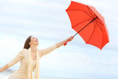 Playful girl joking with umbrella. Playful girl joking with a red umbrella on the beach with the sky in the background Stock Image