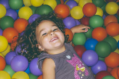 Playful girl lying in ball pit Stock Photography