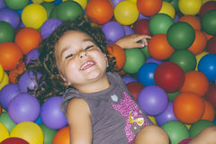 Playful girl lying in ball pit Royalty Free Stock Photography