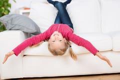 Playful Girl Lying Upside Down On Sofa Stock Image