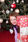 Playful girl peering around stacked gifts Royalty Free Stock Images