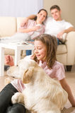 Playful girl petting family dog with parents. Sitting on couch Royalty Free Stock Photo