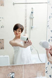 Playful girl posing with hair dryer Stock Images