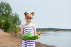 Playful girl posing with paper boat and bubbles Royalty Free Stock Photo