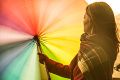 Playful Girl with rainbow unbrella. Beautiful young and smiling red head girl twisting and spinning a rainbow colored umbrella during a sunset in front of the Stock Photos