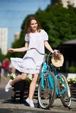 Playful girl in sunlight with retro bike on city street. Playful girl in the sunlight of a summer day with a blue retro bike on the city street Royalty Free Stock Photos