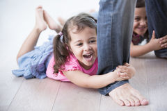 Playful girls holding father's legs on hardwood floor Royalty Free Stock Photography