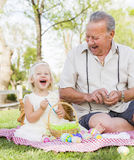 Playful Grandfather and Granddaughter Coloring Easter Eggs on Blanket At Stock Photo