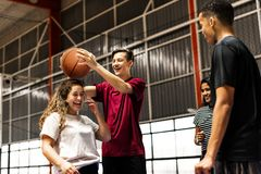 Playful group of teenager friends on a basketball court stock image