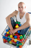 Playful guy in shopping cart Stock Photos