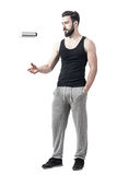 Playful gym male tossing and flipping water bottle container. Stock Photos