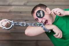 Playful handcuffed male shows funny icon on stick Royalty Free Stock Image
