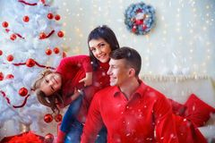 Playful happy family celebrating Christmas. Cheerful men and women with adorable girl posing playfully in sparkles of Christmas adornments Stock Photos