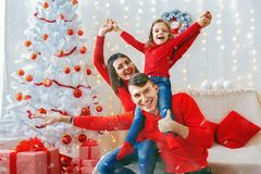 Playful happy family celebrating Christmas. Cheerful men and women with adorable girl posing playfully in sparkles of Christmas adornments Royalty Free Stock Photography