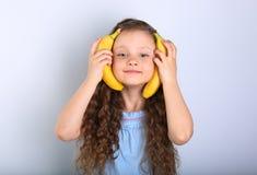 Playful happy fun long hair kid girl holding yellow bright banan Royalty Free Stock Photos