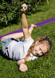 Playful happy little girl resting on a grass in summer park stock photos