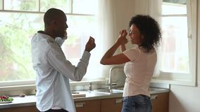 Playful happy young african american couple dancing together in kitchen