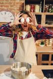 Playful housewife covered her eyes with eggs Royalty Free Stock Images