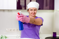Playful housewife taking aim with the detergent Stock Photography