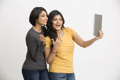 Playful Indian young woman using digital tablet Stock Image
