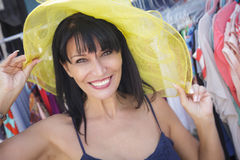 Playful Italian Woman Trying on Yellow Hat at Market Stock Photos