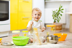 Playful kid boy with face in flour surrounded kitchenware and foodstuffs. Playful kid toddler with face soiled flour. Little boy surrounded kitchenware and stock images