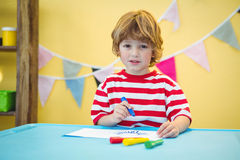 Playful kid colouring in a picture Stock Photo