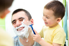 Playful kid and dad shaving together in bathroom Royalty Free Stock Photography