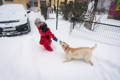 Playful kid and dog. Running in snow during winter Stock Photo