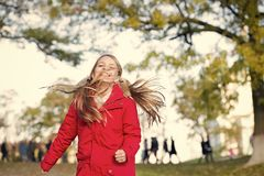 Playful kid leisure. Child blonde long hair walking in warm jacket outdoor. Girl happy in red coat enjoy fall nature. Park. Child wear fashionable coat with royalty free stock photo