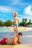 Playful kid pretending he is Statue of Liberty, with father on tropical beach Stock Image