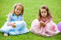 Playful kids. Two little girls are sitting and playing on green grass Royalty Free Stock Photo